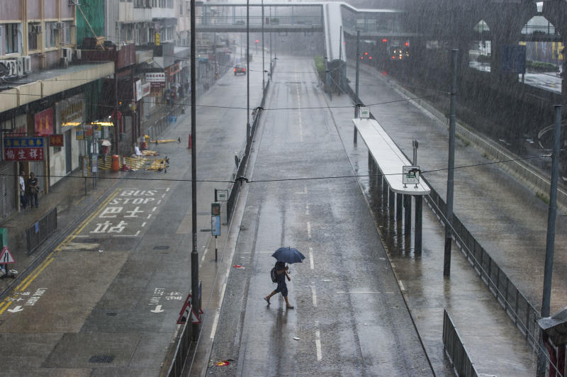 A man walks under the rain in the Sheung Wan district of Hong Kong during a thunderstorm caused by Typhoon Kalmaegi on September 16, 2014 (AFP Photo/Xaume Olleros)