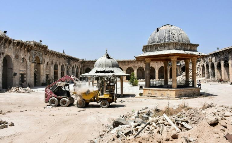 A digger clears rubble from the courtyard of Aleppo's Umayyad Mosque on July 22, 2017