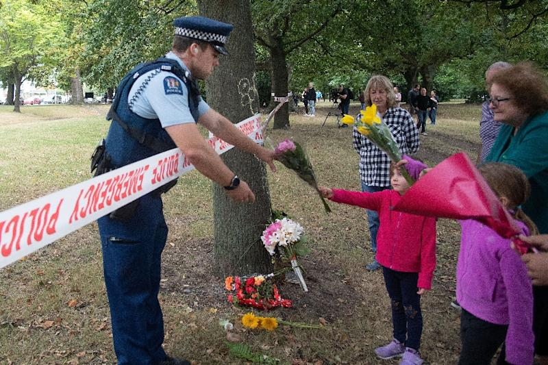 Members of the public hand flowers to a police officer in Christchurch, New Zealand where an attack on two mosques left 50 dead (AFP Photo/Marty MELVILLE)