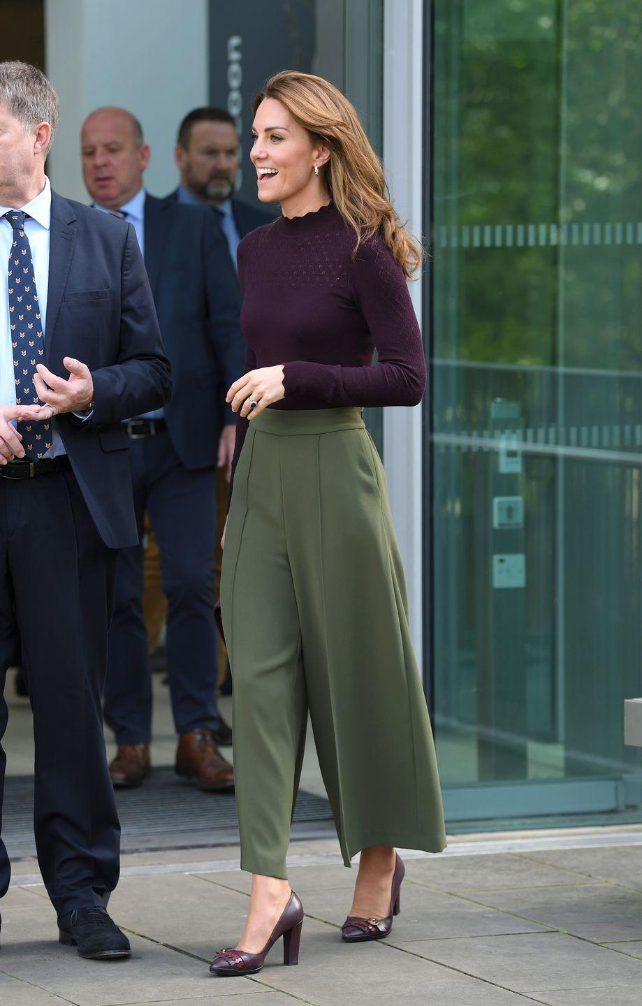 """<p>For a <a href=""""https://www.townandcountrymag.com/style/fashion-trends/a29399497/kate-middleton-chanel-bag-jigsaw-trousers-natural-history-museum-photos/"""" rel=""""nofollow noopener"""" target=""""_blank"""" data-ylk=""""slk:surprise visit to the National History Museum"""" class=""""link rapid-noclick-resp"""">surprise visit to the National History Museum</a>, Middleton wore a burgundy sweater with a scalloped neckline and sleeves, and paired it with olive wide-leg trousers. She added burgundy pumps, gold Asprey hoops, and a Chanel handbag for the quintessential early fall outfit.</p>"""