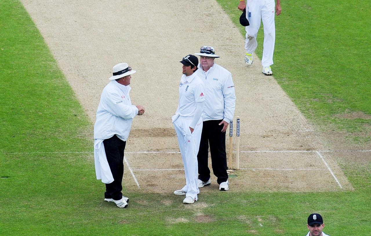 England's captain Alastair Cook speaks with the umpires as rain stops play during the Second Investec Test match at Headingley, Leeds.