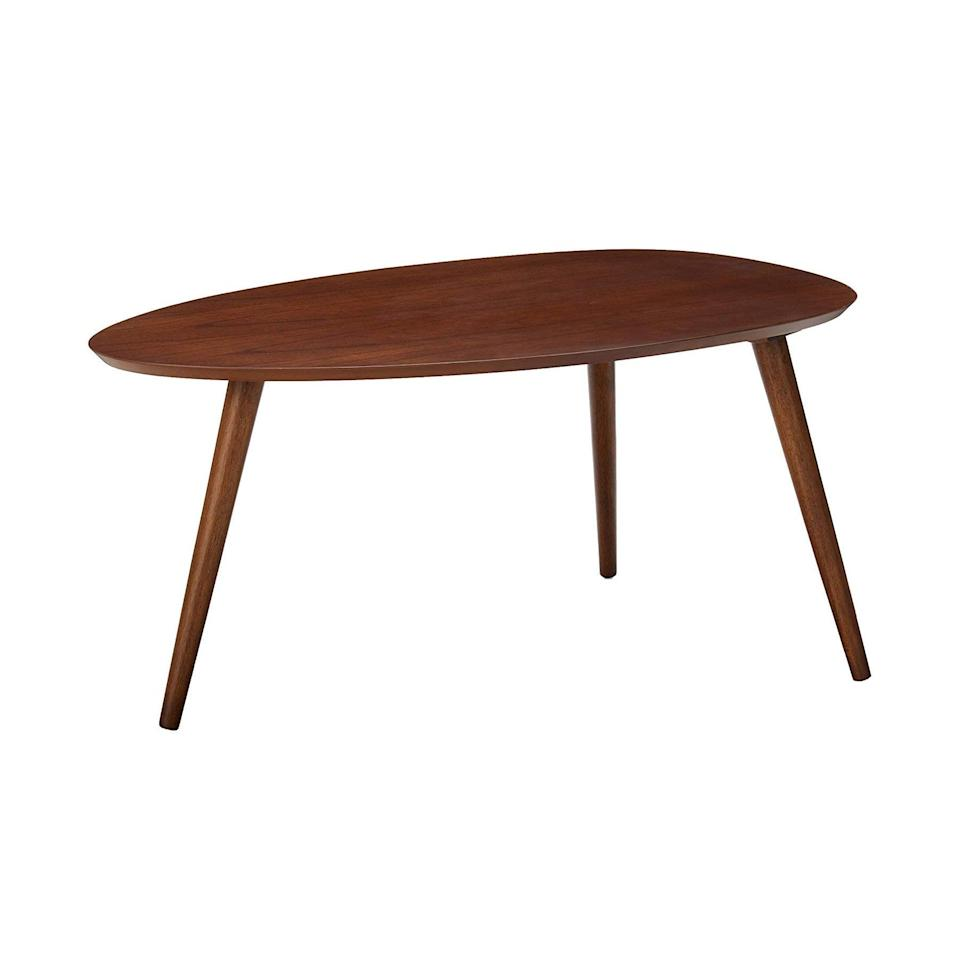 """<h3>Walnut Wood Coffee Table</h3><br>Yes: an egg-shaped, MCM-style coffee table for under $100 exists outside of your wildest design dreams. <br><br><strong>Christopher Knight Home</strong> Caspar Walnut Wood Coffee Table, $, available at <a href=""""https://amzn.to/3sxCnRg"""" rel=""""nofollow noopener"""" target=""""_blank"""" data-ylk=""""slk:Amazon"""" class=""""link rapid-noclick-resp"""">Amazon</a>"""