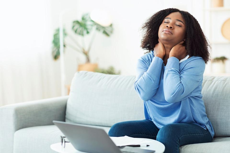 young woman sitting on couch massaging sore neck