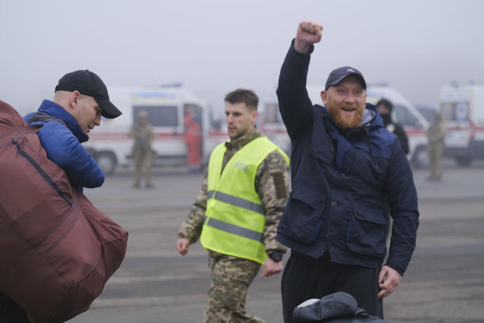 A pro-Russian prisoner makes a fist next to an Ukrainian police officer during a prisoner exchange between Ukrainian and pro-Russian rebels sides, near the Maiorske checkpoint, Donetsk area, Ukraine, Sunday, Dec. 29, 2019. Ukrainian forces and Russia-backed rebels in the east have begun exchanging prisoners in a move aimed at ending their five-year-long war. (Yevgen Honcharenko/Pool Photo via AP)