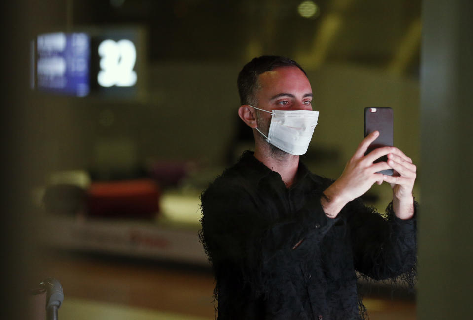 PARIS, FRANCE - FEBRUARY 10: A passenger coming from China, wearing a protective mask uses his cellphone as he leaves the Terminal after landing in Charles De Gaulle Airport on February 10, 2020 in Roissy-en-France. The Coronavirus was first detected in December in Wuhan, the capital of Hubei province, and has left at least 908 dead in mainland China, where the number of infected people exceeds 40,000, according to today's report by the Chinese authorities. The epidemic is spreading worldwide with confirmed cases in more than 25 countries and territories. (Photo by Chesnot/Getty Images)