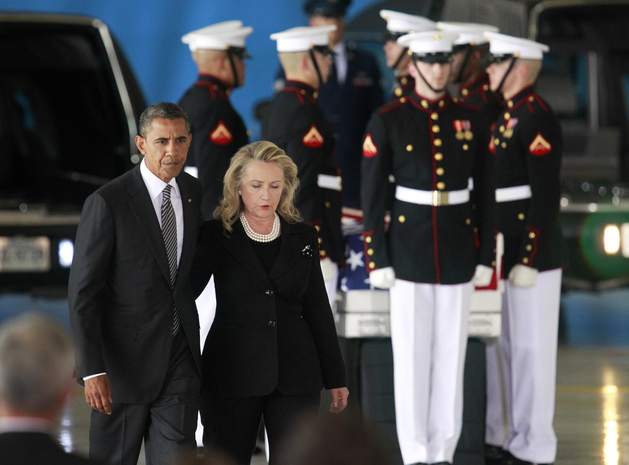 U.S. President Barack Obama walks with Secretary of State Hillary Clinton past the flag-draped transfer case of one of four Americans who died this week in Libya, during a transfer of remains ceremony at Andrews Air Force Base near Washington, September 14, 2012. U.S. Ambassador to Libya Christopher Stevens and three other Americans killed this week in Benghazi were honored at the ceremony.     REUTERS/Jason Reed  (UNITED STATES - Tags: POLITICS)