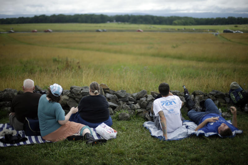 Visitors to Gettysburg National Military Park sit at a wall held by Union forces ahead of a commemorative march where Pickett's Charge took place during ongoing activities commemorating the 150th anniversary of the Battle of Gettysburg, Wednesday, July 3, 2013, at in Gettysburg, Pa. Union forces turned away a Confederate advance in the pivotal battle of the Civil War fought July 1-3, 1863, which was also the war's bloodiest conflict with more than 51,000 casualties. (AP Photo/Matt Rourke)