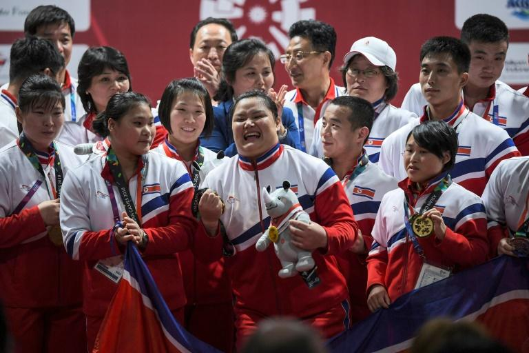 Gold medallist North Korea's Kim Kuk Hyang celebrates with teammates during the awards ceremony for the women's +75kg weightlifting event