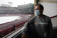 Boston Marathon Race Director Dave McGillivray looks out at the snow covered field at Fenway Park, Thursday, Jan. 28, 2021, at Fenway Park in Boston. Since the 2021 Boston Marathon is on hold until fall, McGillivray has been tapped by the state of Massachusetts to run mass vaccination operations at Gillette Stadium and Fenway Park. Event organizers and other unconventional logistics experts are using their skills to help the nation vaccinate as many people as possible. (AP Photo/Charles Krupa)