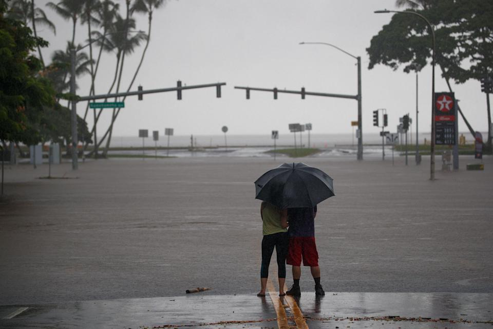 <p>Michelle Montgomery (L) and Eric Leifer (R) share a moment under an umbrella, as they view the flooded Pauahi St and Kamehameha Ave intersection in Hilo, Hawaii, Aug. 24, 2018. (Photo: Bruce Omori/EPA-EFE/REX/Shutterstock) </p>