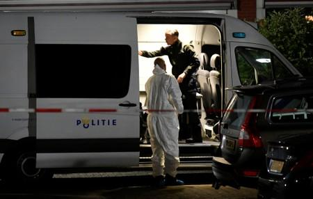Forensic technician stands next to a police van following a shooting in Dordrecht