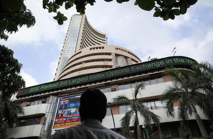 A man looks at a screen across the road displaying the election results on the facade of the Bombay Stock Exchange (BSE) building in Mumbai May 16, 2014. REUTERS/Danish Siddiqui/Files
