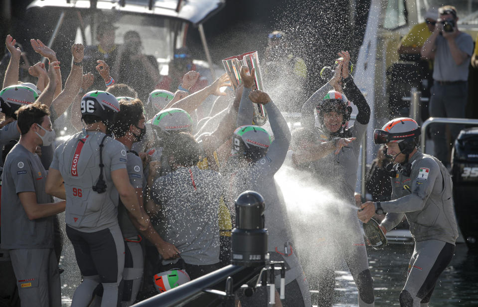 Italy's Luna Rossa team celebrate after defeating Britain's INEOS Team UK in race eight of the Prada Cup on Auckland's Waitemata Harbour, New Zealand, Sunday, Feb.21, 2021. Italian challenger Luna Rossa Prada Pirelli will race defender Emirates Team New Zealand in the 36th match for the America's Cup after beating Britain's Ineos Team UK in two races Sunday to seal a 7-1 win in the best-of-13 race challengers series final. (Alex Burton/NZ Herald via AP)