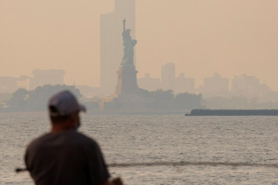 Image: The Statue of Liberty is seen through a cover of wildfire smoke in New York Harbor as seen from Brooklyn, New York (Brendan McDermid / Reuters)