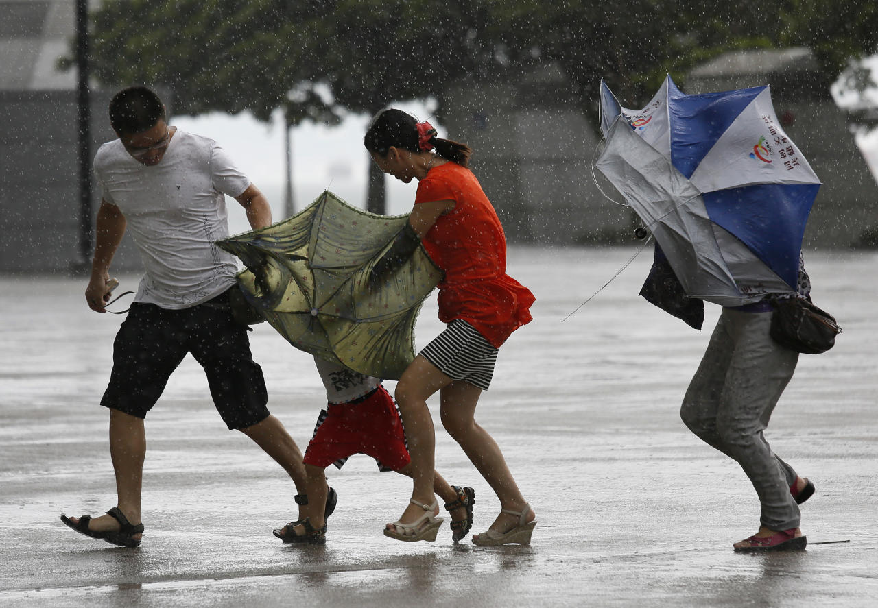 <p> A family battle against the strong wind near the waterfront in Hong Kong Wednesday, Aug. 14, 2013. Typhoon Utor lashed Hong Kong with wind and rain, closing down the bustling Asian financial center Wednesday before sweeping toward mainland China. (AP Photo/Vincent Yu)