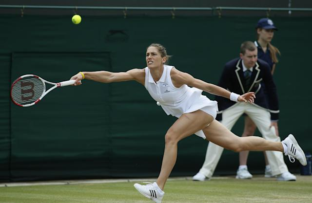 Andrea Petkovic of Germany stretches as she plays a return to Eugenie Bouchard of Canada during their women's singles match at the All England Lawn Tennis Championships in Wimbledon, London, Saturday, June 28, 2014. (AP Photo/Alastair Grant)