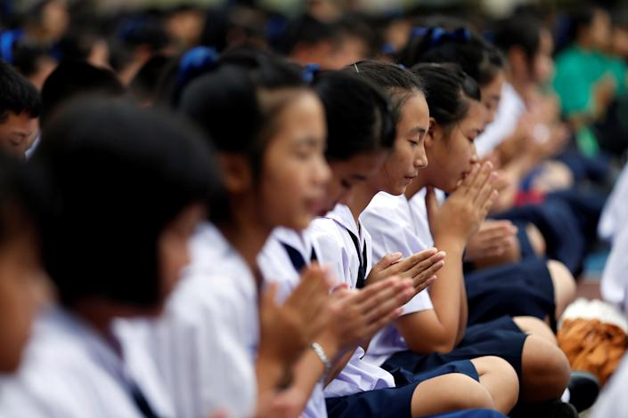 <p>Students pray in Mae Sai Prasitsart school on July 2, 2018, during the search for members of a youth soccer team and their coach who went missing in a flooded cave, in the northern province of Chiang Rai, Thailand. (Photo: Soe Zeya Tun/Reuters) </p>