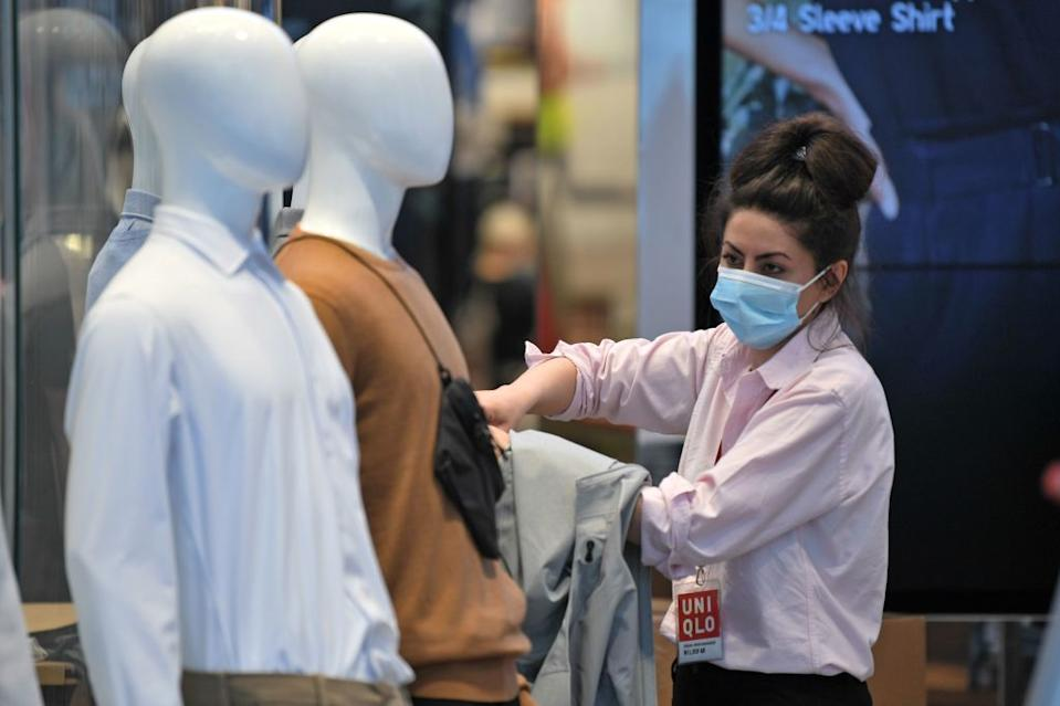 A shop worker gets ready to welcome customers to Uniqlo in London. (Getty Images)