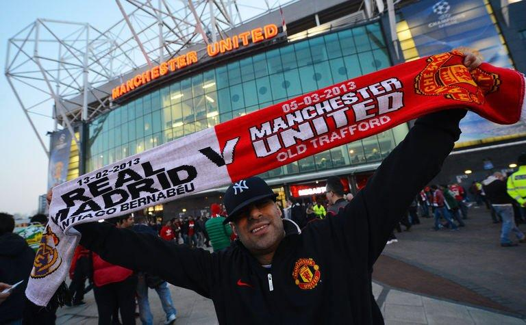 A Real Madrid supporter poses holds up hisscarf ahead of the Champions League last-16 second leg between Manchester United and Real Madrid at Old Trafford in Manchester, north-west England, on March 5, 2013. The tie is poised at 1-1 from the first leg at the Bernabeu