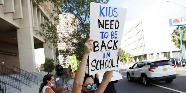 """A protester holds a sign calling for schools to reopen seen on August 6, 2020 in Tampa, Florida. <p class=""""copyright"""">Octavio Jones/Getty Images</p>"""