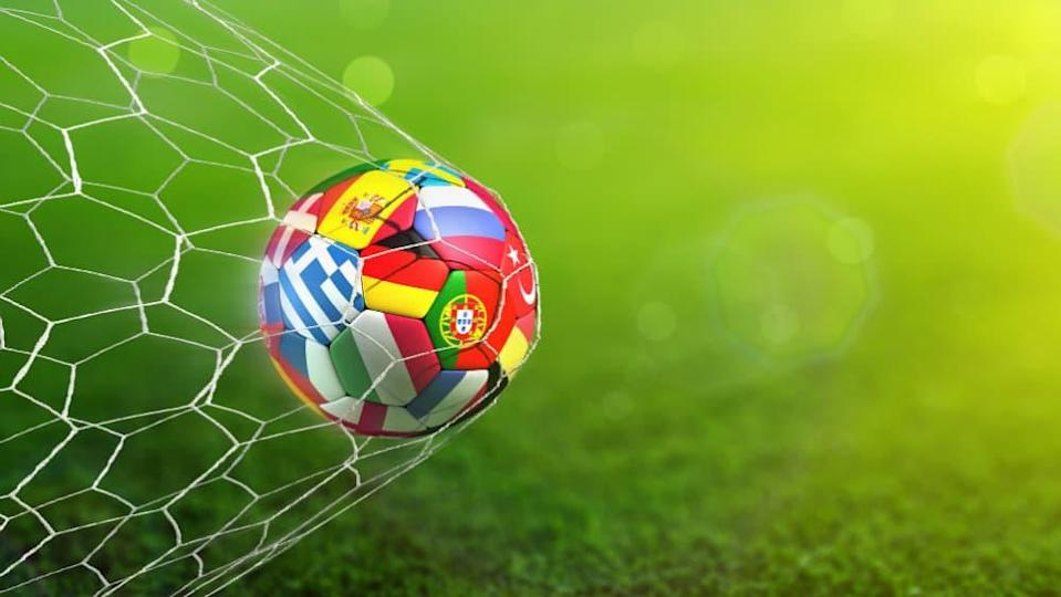 Ball with european flags in the net with green field background