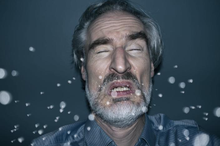 """<span class=""""caption"""">When a person sneezes, tiny droplets, or aerosols, can linger in the air.</span> <span class=""""attribution""""><a class=""""link rapid-noclick-resp"""" href=""""https://www.gettyimages.com/detail/photo/sneezing-man-royalty-free-image/1209729560"""" rel=""""nofollow noopener"""" target=""""_blank"""" data-ylk=""""slk:Jorg Greuel via Getty Images"""">Jorg Greuel via Getty Images</a></span>"""