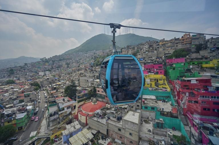 Passengers travel over Mexico City on the new Cablebus aerial tramway