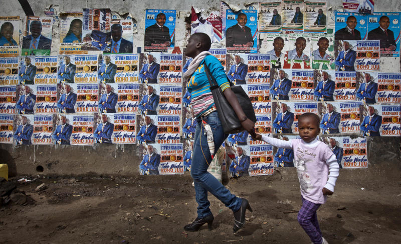 FILE - In this Feb. 26, 2013 file photo, a mother and her child walk past a wall plastered with election campaigning posters in the Mathare slum of Nairobi, Kenya. The toll of more than 1,000 dead after Kenya's last election makes the presidential vote on Monday, March 4, 2013 the most important in the country's 50-year history, while a slate of new races and a presidential candidate Uhuru Kenyatta who faces charges at the International Criminal Court also make it Kenya's most complicated. (AP Photo/Ben Curtis, File)