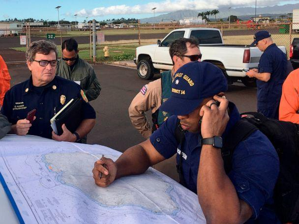 PHOTO: Coast Guard Incident Command Post responders look over a map of the Na Pali Coast State Wilderness Park on the Hawaiian island of Kauai on Friday, Dec. 27, 2019, the day after a tour helicopter disappeared with seven people aboard. (U.S. Coast Guard via AP)