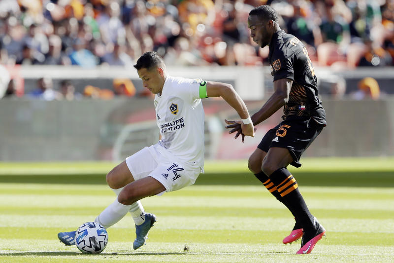 """Los Angeles Galaxy forward Javier """"Chicharito"""" Hernandez (14) moves the ball past Houston Dynamo defender Maynor Figueroa (15) during the first half of an MLS soccer match Saturday, Feb. 29, 2020, in Houston. (AP Photo/Michael Wyke)"""