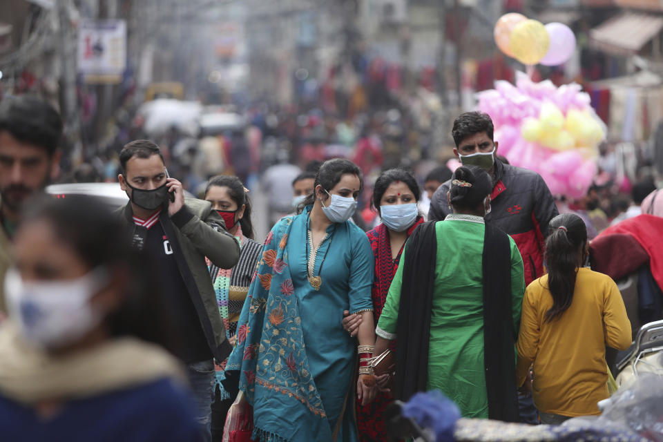 Indians, most of them, wearing face masks as a precautionary measure against the coronavirus crowd a Sunday market in Jammu, India, Sunday, Nov.22, 2020. (AP Photo/Channi Anand)