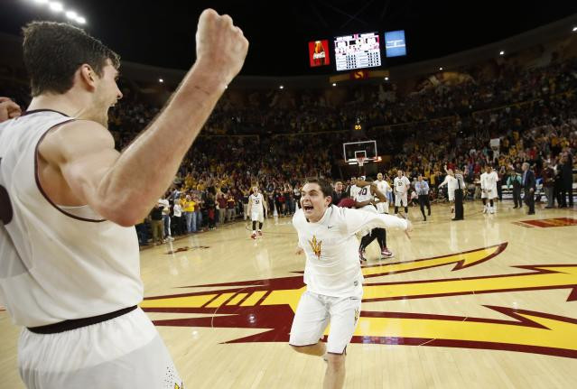 Arizona State's Jordan Bachynski, left, celebrates with teammate Jarett Upchurch, right, just prior to time expiring during the second overtime against Arizona during an NCAA college basketball game, Friday, Feb. 14, 2014, in Tempe, Ariz. Arizona State defeated Arizona 69-66 in double overtime. (AP Photo/Ross D. Franklin)