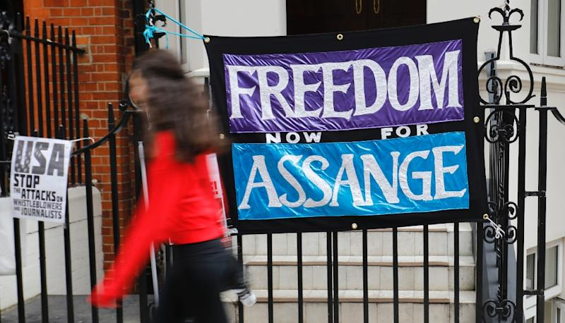 "A pedestrian passes a banner reading ""Freedom for Assange"" outside the Ecuadorian Embassy in London where WikiLeaks founder Julian Assange has resided to avoid arrest since 2012 (AFP Photo/Tolga AKMEN)"