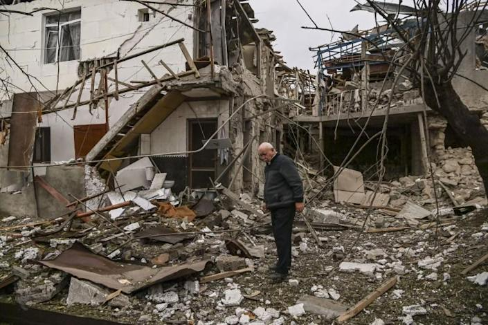 An elderly man stands in front of a destroyed house in the Nagorno-Karabakh region's main city of Stepanakert.