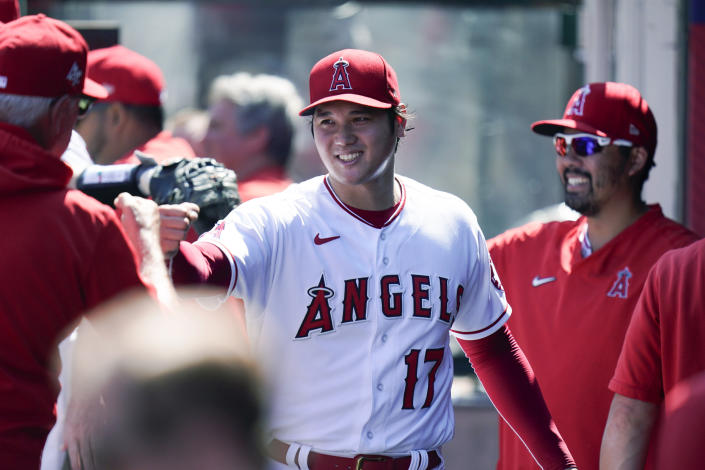 Los Angeles Angels starting pitcher Shohei Ohtani, of Japan, is greeted by manager Joe Madden in the dugout after the third inning of a baseball game Sunday, Sept. 19, 2021, in Anaheim, Calif. (AP Photo/Jae C. Hong)