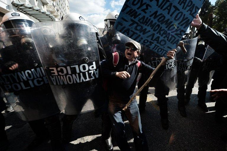 A demonstrator tries to pass a riot police cordon during a 24-hour general strike in Athens on February 20, 2013