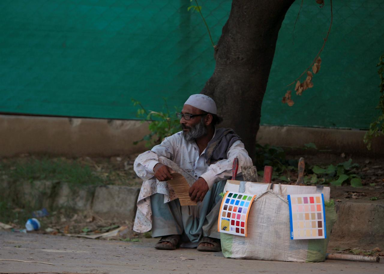 A labourer sits with his tools along a roadside while waiting for work in Islamabad, Pakistan July 29, 2016. REUTERS/Faisal Mahmood