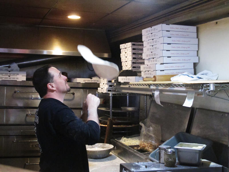In this March 24, 2020, photo, Michael Morin, co-owner of Federico's Pizza in Belmar N.J., makes a pizza. Morin and his brother Bryan took out a $50,000 line of credit to ensure that their 20 employees can stay on the payroll for at least two months during the virus outbreak. That prompted an outpouring of donations from customers wanting to send pizzas to hospital workers and first responders. (AP Photo/Wayne Parry)