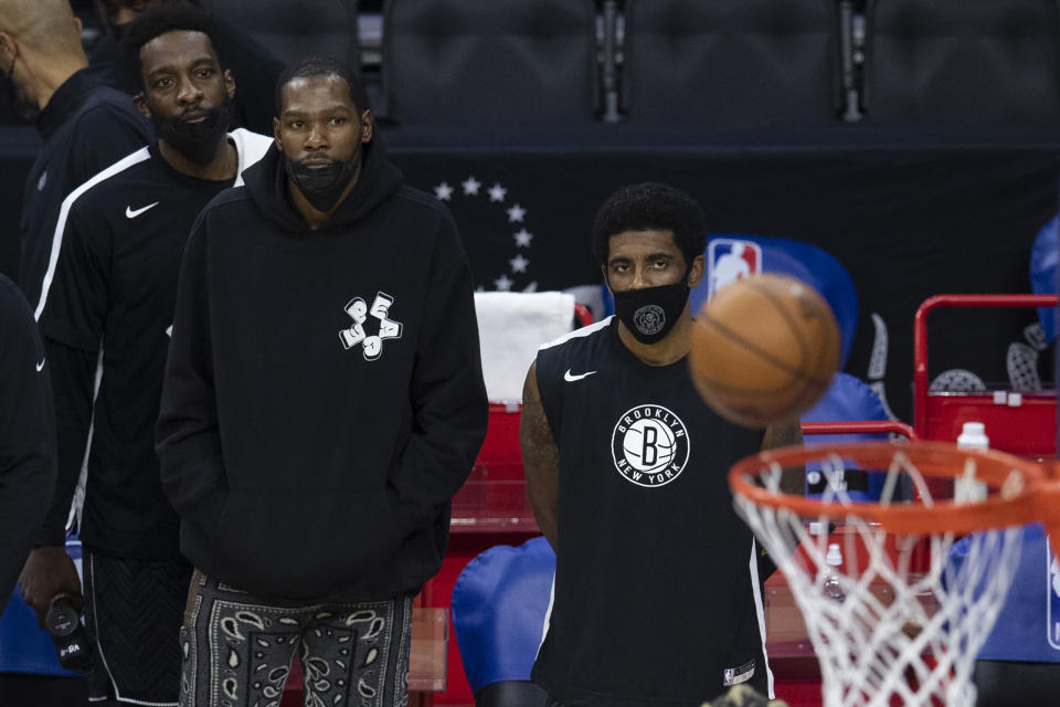 Kevin Durant and Kyrie Irving watch from the sidelines as their Brooklyn Nets lose to the Philadelphia 76ers in a game that tilted the standings. (Mitchell Leff/Getty Images)