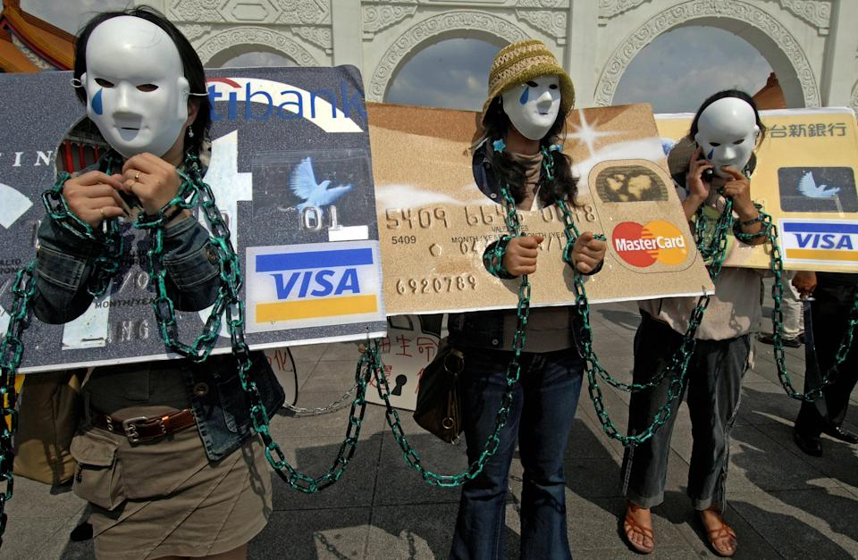 """Local consumers who are in credit card debt, referred to as """"credit card slaves"""", take part in a demonstration calling for the government to pass a law to help people owing money to banks. (Photo credit: SAM YEH/AFP via Getty Images)"""