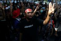 People show the three-finger salute in Bangkok