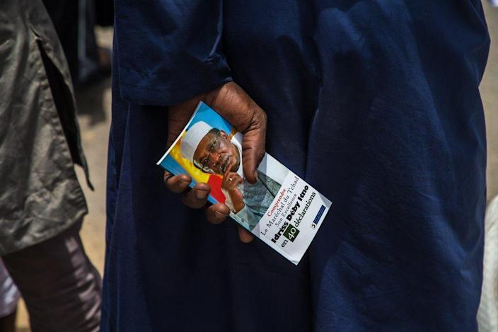 A man holds a memorial book in his hands at the funeral.