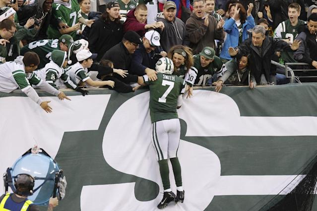 New York Jets quarterback Geno Smith (7) celebrates with fans after scoring a touchdown during the second half of an NFL football game against the Cleveland Browns, Sunday, Dec. 22, 2013, in East Rutherford, N.J. The Jets won the game 24-13. (AP Photo/Peter Morgan)