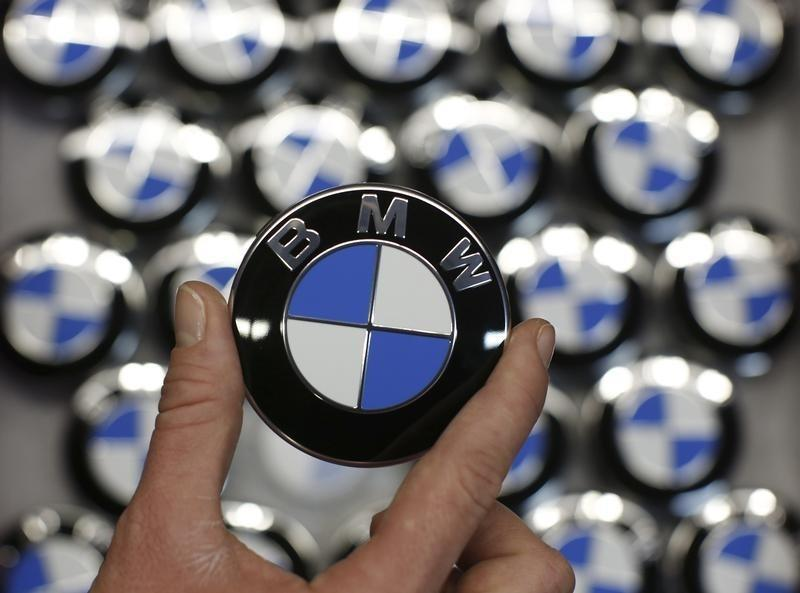 An employee holds BMW logo on production line of BMW C evolution electric maxi-scooter at BMW motorcycle plant in Berlin