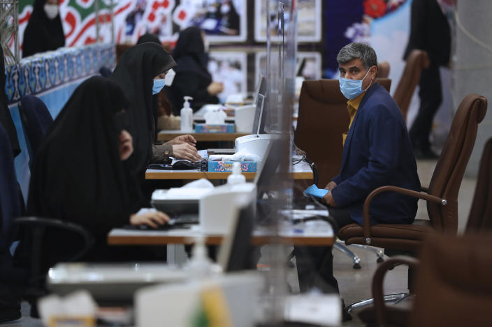 An unidentified man sits while an election headquarters staff member registers his name as a candidate for the June 18, presidential elections at the interior Ministry in Tehran, Iran, Tuesday, May 11, 2021. Iran opened registration Tuesday for potential candidates in the country's June presidential election, kicking off the race as uncertainty looms over Tehran's tattered nuclear deal with world powers and tensions remain high with the West. (AP Photo/Vahid Salemi)