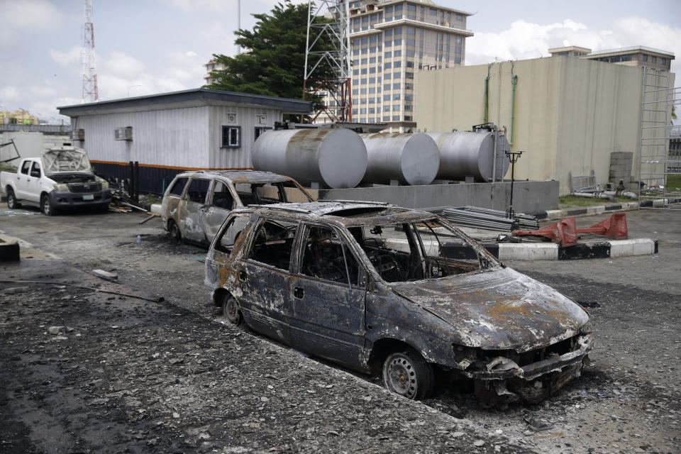Burnt vehicles are seen near the Lekki toll gate, in Lagos, Friday, Oct. 23, 2020. Resentment lingered with the smell of charred tires Friday as Nigeria's streets were relatively calm after days of protests over police abuses, while authorities gave little acknowledgement to reports of the military killing at least 12 peaceful demonstrators earlier this week. (AP Photo/Sunday Alamba)