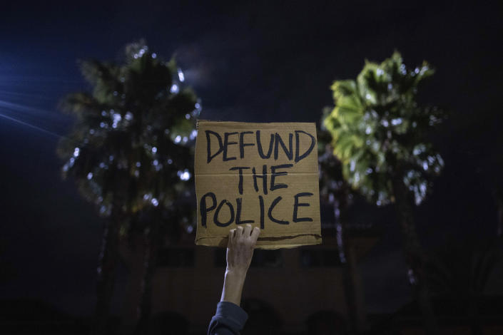 A protester holds up a sign as a police helicopter flies by in front of the South Los Angeles Sheriff's Department during protests following the death of Dijon Kizzee on Monday, Aug. 31, 2020, in Los Angeles, Calif. (AP Photo/Christian Monterrosa)