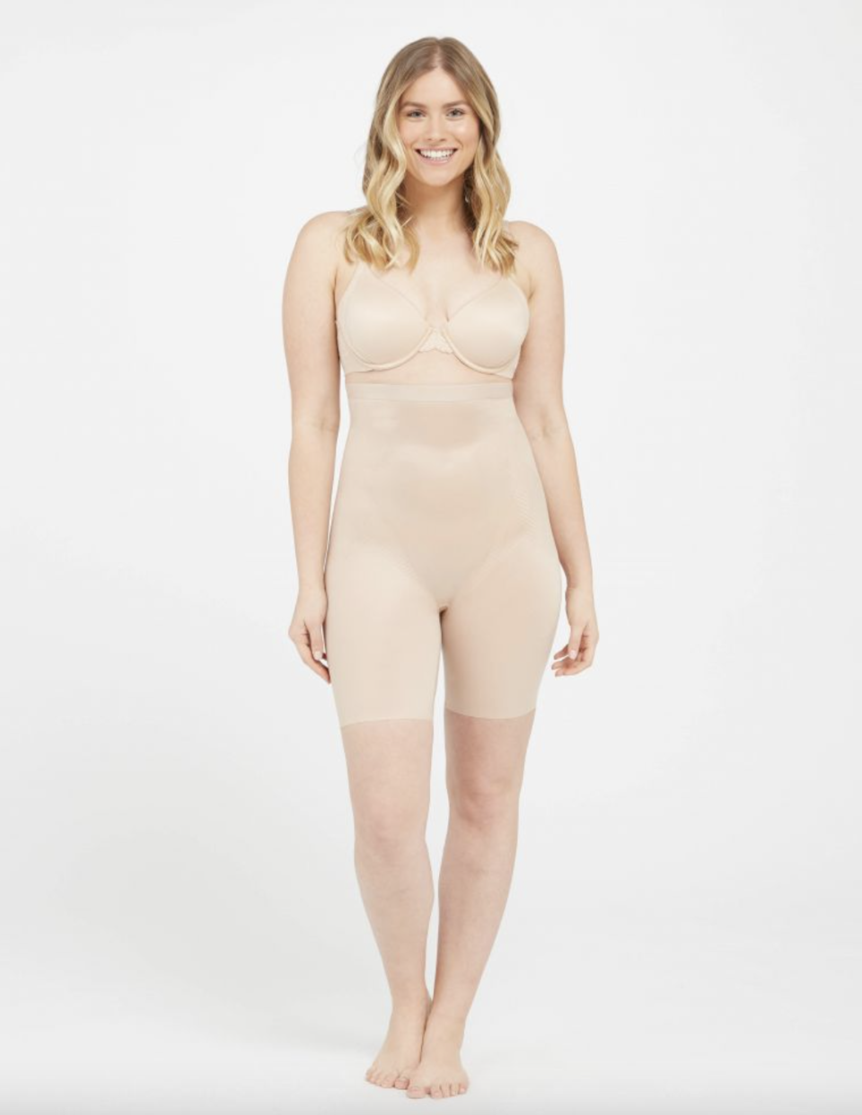 blonde model wearing Spanx Thinstincts 2.0 High-Waisted Mid-Thigh Short in Champagne Beige and nude bra(Photo via Spanx)