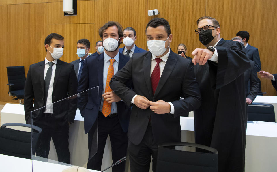 Paulo Richardo Rocha Pinto, husband of a victim, lawyer Pedro Martins, Gustavo Barroso Camara, brother of a victim, and lawyer Jan Erik Spangenberg, from left, arrive in the courtroom at the Munich Regional Court before the start of the trial in Munich, Germany, Tuesday, Sept.28, 2021. Following the dam disaster in Brumadinho, Brazil, in early 2019, the affected community and the family of one of the 260 fatalities sued TUEV Sued for damages. (Sven Hoppe/dpa via AP)