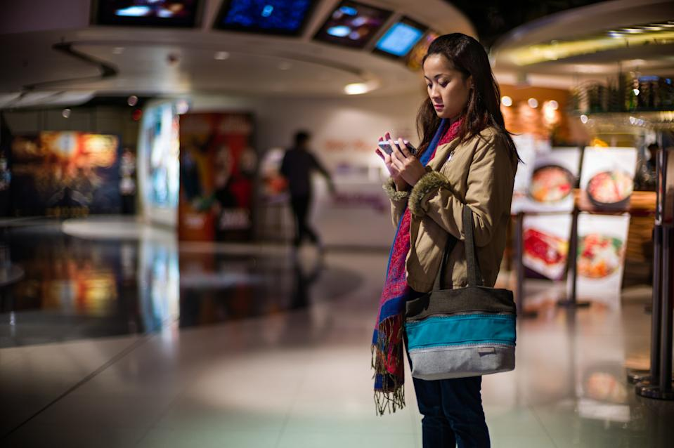 Pretty young lady using a smartphone while waiting to get into the cinema for a movie.